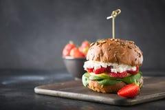 Veggie, Burger des strengen Vegetariers mit Erdbeere, Birne, Hüttenkäse und Spinat auf frischem Brötchen auf Schwarzem stockfoto