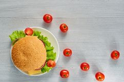Veggie burger with fresh ingredients on the gray concrete background with free copy space. Vegetarian sandwich. Decorated with cherry tomatoes. Top view Royalty Free Stock Photo