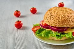 Veggie burger with salad, onion rings and cheese decorated with fresh cherry tomatoes on the gray concrete background. With free copy space. Side view Stock Photo