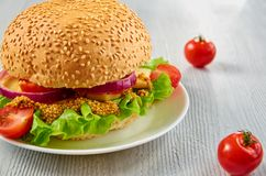 Veggie burger with salad, onion rings decorated with fresh cherry tomatoes on the gray concrete background with free copy space. Vegetarian sandwich. Close up royalty free stock photography