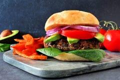 Veggie burger with sweet potato fries on a dark background. Vegetarian bean burger with avocado, spinach and sweet potato fries against a dark background Stock Photo