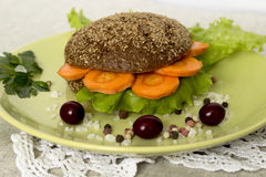 Veggie burger. Vegetarian burger with carrots, lettuce and cranberry on a green plate Royalty Free Stock Image