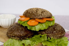 Veggie burger. Vegetarian burger with carrots and lettuce on a wooden stand Stock Photo