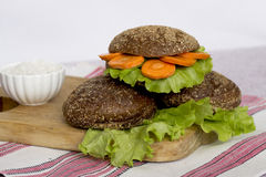 Veggie burger. Vegetarian burger with carrots and lettuce on a wooden stand Royalty Free Stock Photos