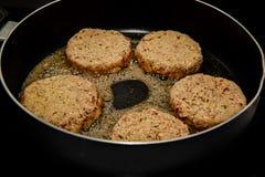 Veggie estropeado Bean Burgers In Frying Pan imagenes de archivo