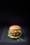Veggie falafel burger with pesto sauce, tomato, cress salad and onion on black slate board. Space for text. Royalty Free Stock Images