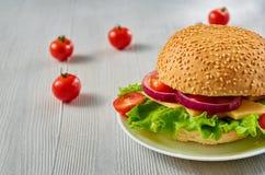 Veggie hamburger z sałatką, cebulkowi pierścionki i ser dekorujący z świeżymi czereśniowymi pomidorami na szarość, betonujemy tło Zdjęcie Stock