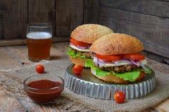Veggie hamburgery z kotlecikiem oberżyna, sałata, kiszone cebule, pomidor na brown drewnianym tle Jarski lunchu lub gościa restau Fotografia Stock
