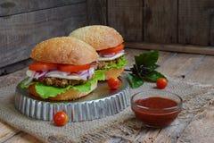 Veggie hamburgery z kotlecikiem oberżyna, sałata, kiszone cebule, pomidor na brown drewnianym tle Jarski lunchu lub gościa restau Zdjęcie Stock