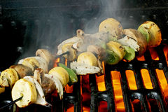 Veggie Kabobs. Cut up vegetables on metal skewers cooking on grill; smoke and fire Royalty Free Stock Photo