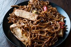 Veggie Noodle with Tofu and Red Peppers on Black Plate stock photography