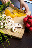 Veggie salad. Woman prepares mushrooms, pepper and radish for a salad on a wooden cutting board Stock Photo