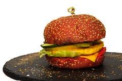 Veggieburger mit Käse, Gurken, Gemüsepaprikas auf einem schwarzen Steinflacheisen lizenzfreies stockbild