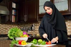 Veggies вырезывания hijab аравийской женщины нося в кухне стоковые изображения rf