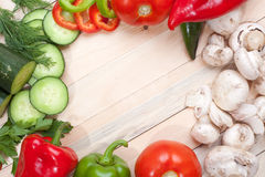 Veggies. Overhead shot of sliced and whole veggies on wooden table top with empty space for text Stock Image