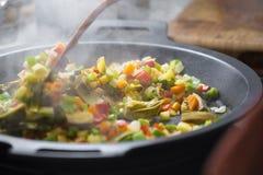 Veggies de mélange de cuillère en bois sur une casserole Image libre de droits