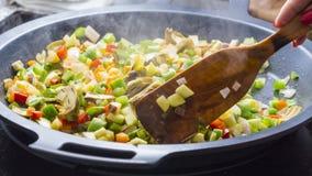 Veggies de mélange de cuillère en bois sur une casserole Photographie stock