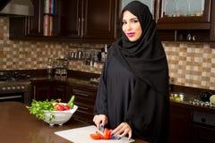 Veggies de port de coupe de hijab de femme Arabe dans la cuisine Photos libres de droits