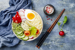 Veggies detox Buddha bowl recipe with egg, carrots, sprouts, couscous, cucumber, radishes, seeds. Top view, flat lay, copy space Royalty Free Stock Image