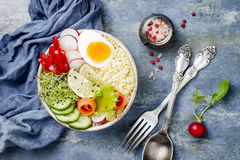 Veggies detox Buddha bowl recipe with egg, carrots, sprouts, couscous, cucumber, radishes, seeds. Top view, flat lay, copy space. Veggies detox Buddha bowl Stock Images