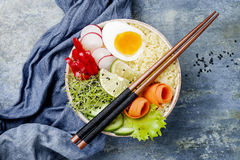 Veggies detox Buddha bowl recipe with egg, carrots, sprouts, couscous, cucumber, radishes, seeds. Top view, flat lay, copy space. Veggies detox Buddha bowl Royalty Free Stock Image