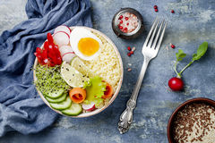 Veggies detox Buddha bowl recipe with egg, carrots, sprouts, couscous, cucumber, radishes, seeds. Top view, flat lay, copy space. Veggies detox Buddha bowl Stock Image