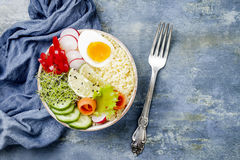 Veggies detox Buddha bowl recipe with egg, carrots, sprouts, couscous, cucumber, radishes, seeds. Top view, flat lay, copy space. Veggies detox Buddha bowl Royalty Free Stock Photography