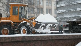 Vehículo de la retirada de la nieve que quita nieve en ciudad almacen de video