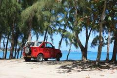 Vehículo rojo en la playa Imagenes de archivo