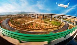 vehículos de la Ciudad-carretera debajo del cielo azul, el vuelo del aeroplano foto de archivo libre de regalías