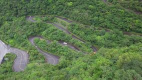 Vehículos que se mueven a lo largo del camino Serpentinous curvado entre el borrachín verde Forest Trees en parque nacional de la metrajes