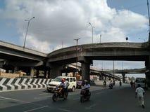 Vehículos y gente que caminan debajo del puente imagen de archivo