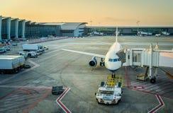 Veh?culos del servicio del aeroplano y del aeropuerto cerca del terminal en la puesta del sol, concepto del d?a de fiesta imagen de archivo libre de regalías