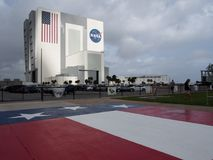 Vehicle Assembly Building at Cape Canaveral. The Sun shining on the Vehicle Assembly Building at Cape Canaveral. An American flag painted on the ground Royalty Free Stock Photography