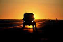 Vehicle backlit by rising sun. Vehicle back lit by rising sun during sunset in Saskatchewan Canada stock photo