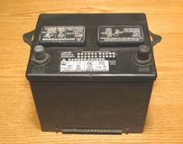 Vehicle battery. Closeup of black battery on wood surface table Royalty Free Stock Images