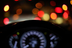 Vehicle car steering wheel and blur bokeh abstract background. Drive vehicle car travel road trip at city night with traffic light on street, image focus Stock Image