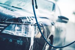 Vehicle in the Car Wash. Covered by Active Washing Foam Stock Image