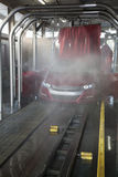 Vehicle on conveyor belt moving through car wash process Royalty Free Stock Photos