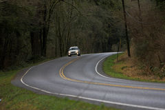 Vehicle on country road. A view of an automobile coming to a curve as it travels along a country road on a cloudy day in Washington state (USA Royalty Free Stock Photos