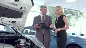 Vehicle dealer Explaining car specifiaction to young woman. stock footage