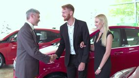 Vehicle dealer passing keys from new car to happy young couple. stock video