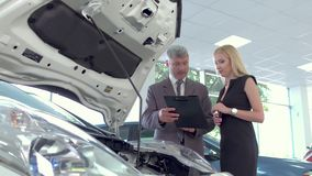 Vehicle dealer selling electric car to young pretty woman. In auto showroom sales manager showing car to customer stock footage