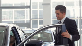 Vehicle dealer showing new car. Car Showroom. Vehicle Dealer Showing Young Man New Car. Auto business, car sale, technology and people concept - happy male with stock video