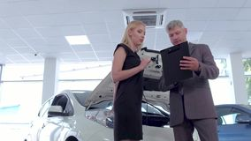 Vehicle dealer and young woman in auto showroom. stock footage