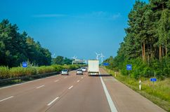 Vehicle Driving on Freeway Towards Wind Turbines Stock Photo