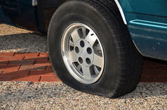 Vehicle with flat tire. Automobile with a flat tire on a city street Royalty Free Stock Photography