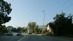 Vehicle going down highway, about to enter city, travelling, front seat view. Stock footage stock video footage