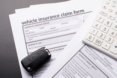 Vehicle Insurance Form. With car keys and calculator on gray table Royalty Free Stock Photo