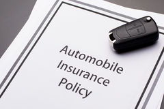 Vehicle Insurance Policy. With car keys on gray table Royalty Free Stock Photos